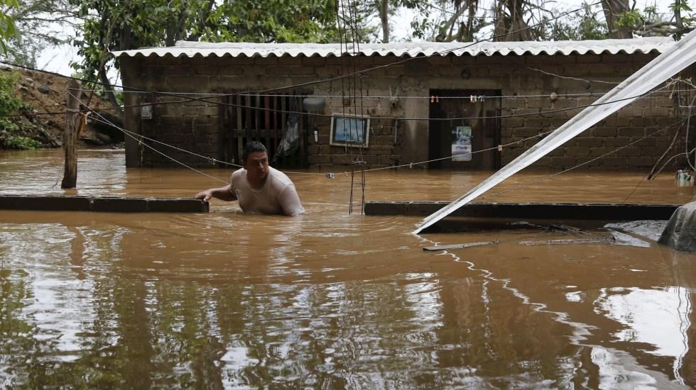 Por paso de Hernán, advierten en cinco estados por lluvias torrenciales en las próximas horas - Personas rescatan pertenencias tras inundación debido al ciclón Hernán, en Melaque. Foto de EFE/Francisco Guasco.