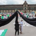 Despliegan enorme moño negro en el Zócalo en protesta por muertes por COVID-19