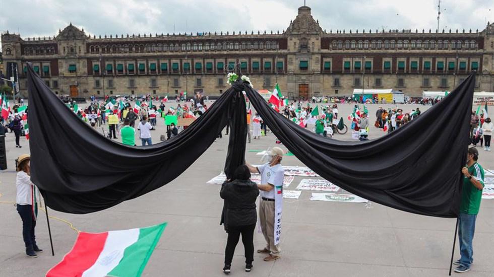 Despliegan enorme moño negro en el Zócalo como protesta por muertes por COVID-19 - Moño negro en manifestación contra el Gobierno Federal por muertes derivadas del COVID-19. Foto de EFE