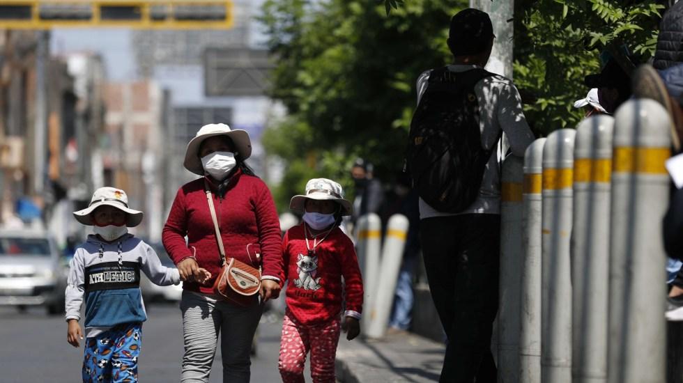 Se asienta COVID-19 en América Latina; México, Perú y Colombia rebasan los 500 mil contagios - Mujer con sus hijos en calles de Perú durante pandemia de COVID-19. Foto de EFE