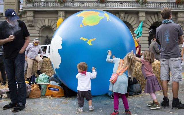 """ONU advierte que informe sobre cambio climático es un """"código rojo para la humanidad"""" - Activistas contra la crisis climática ocupan la plaza Bundesplatz frente al Parlamento suizo, durante la semana de acción 'Levántate por el cambio', en Berna, Suiza. Foto de EFE"""