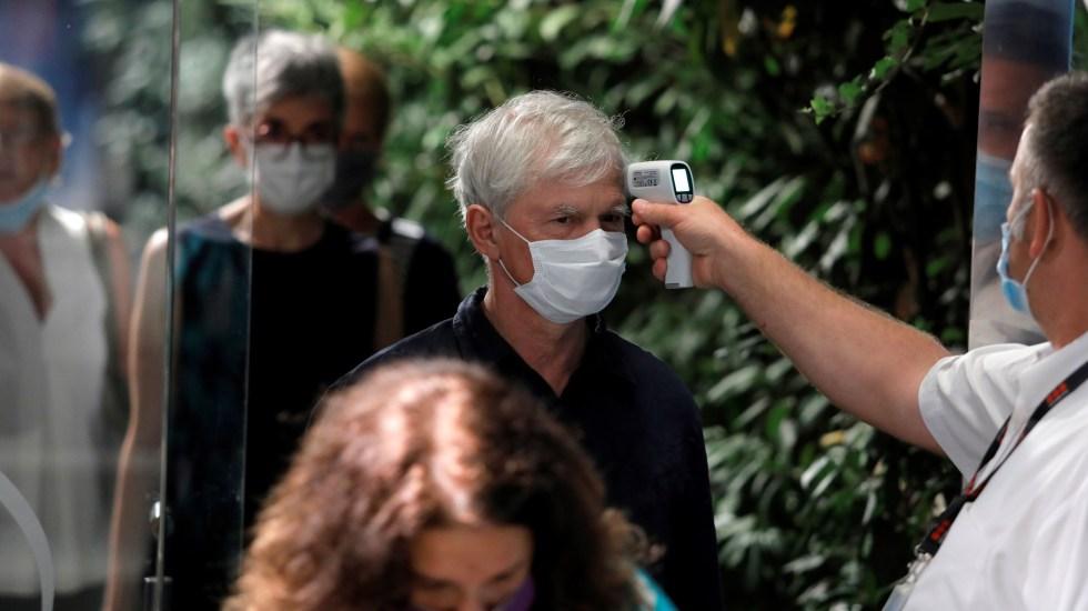El mundo supera los 30 millones de casos de COVID-19 - Toma de temperatura a hombre en Belgrado para detectar posibles síntomas de COVID-19. Foto de EFE