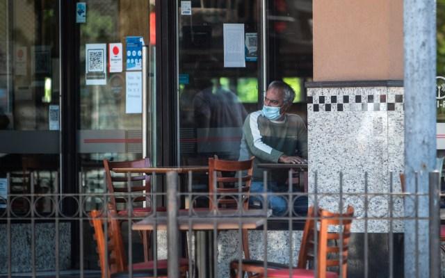 Presidente de Argentina descarta devaluar moneda - Un hombre protegido con tapabocas observa la calle desde el interior de un bar hoy, en Buenos Aires, Argentina. Foto de EFE