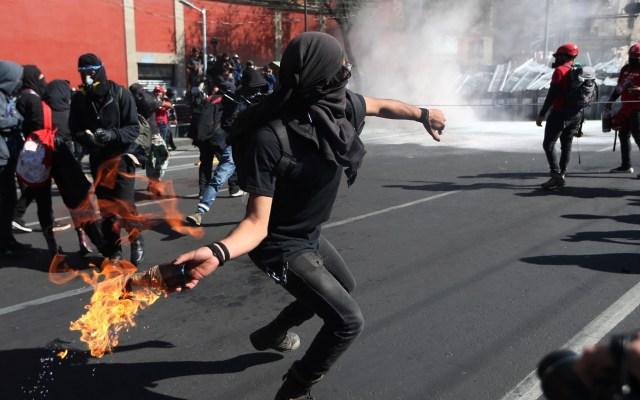 Seis heridos en CDMX durante marcha por el 2 de octubre - Encapuchado arroja bomba molotov a policías sobre Eje Central. Foto de EFE