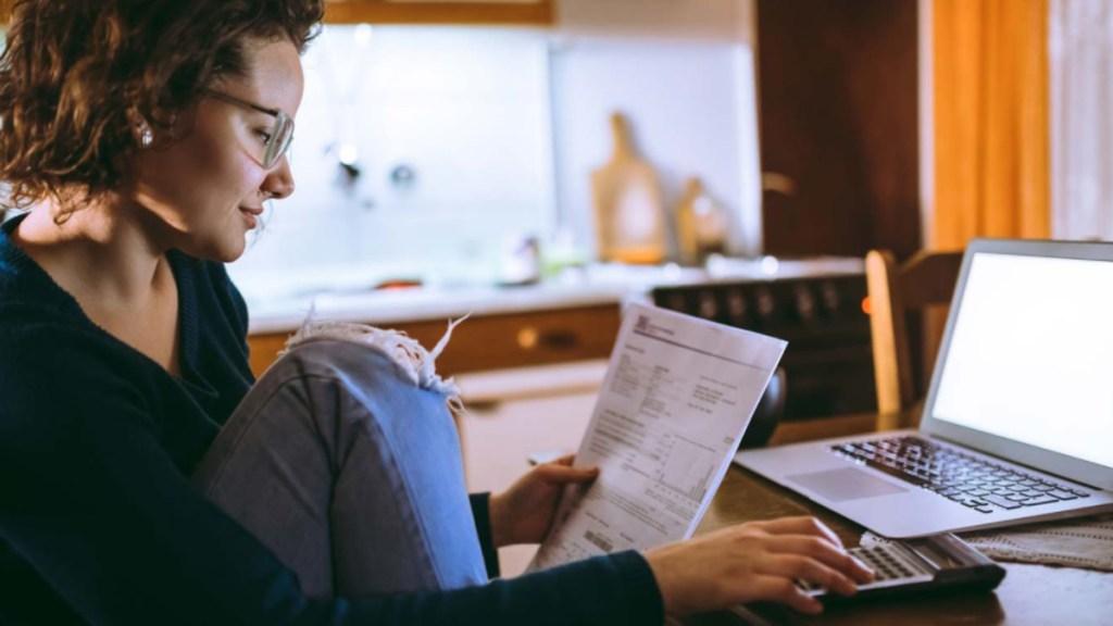 No hay barreras para cumplir tus metas: invierte sin sacrificar gastos y desde tu celular - Mujer revisa sus finanzas Foto de Citibanamex