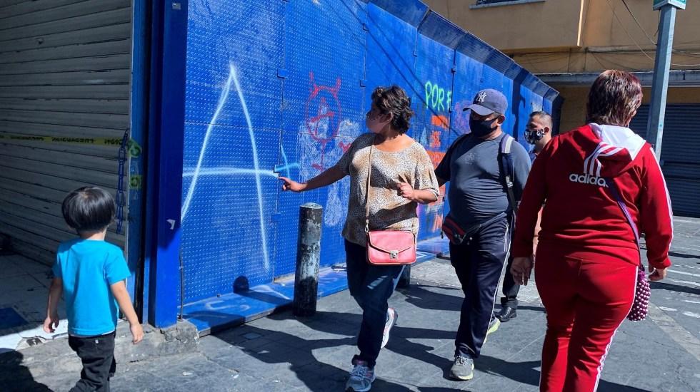 Al límite de hospitalizaciones por COVID-19 en la CDMX, afirma Claudia Sheinbaum - Peatones pasan frente a uno de los cierres parciales con vallas de las principales calles del centro Histórico, para evitar la aglomeración y reducir la cifra de contagios de personas debido a la pandemia de COVID-19, en Ciudad de México. foto de EFE/José Pazos.