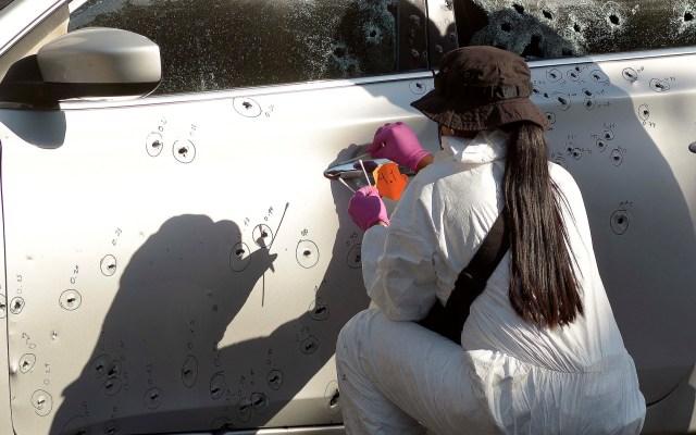 Alianza Federalista exige a AMLO estrategia clara y coordinada de combate a la violencia - Perito forense contabiliza impactos de bala a auto, en homicidio en Sinaloa. Foto de EFE