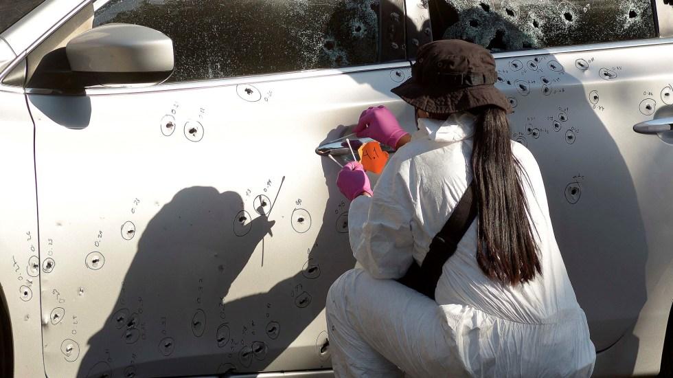 Suman 85 mil 507 homicidios dolosos en lo que va del sexenio - Perito forense contabiliza impactos de bala a auto, en homicidio en Sinaloa. Foto de EFE