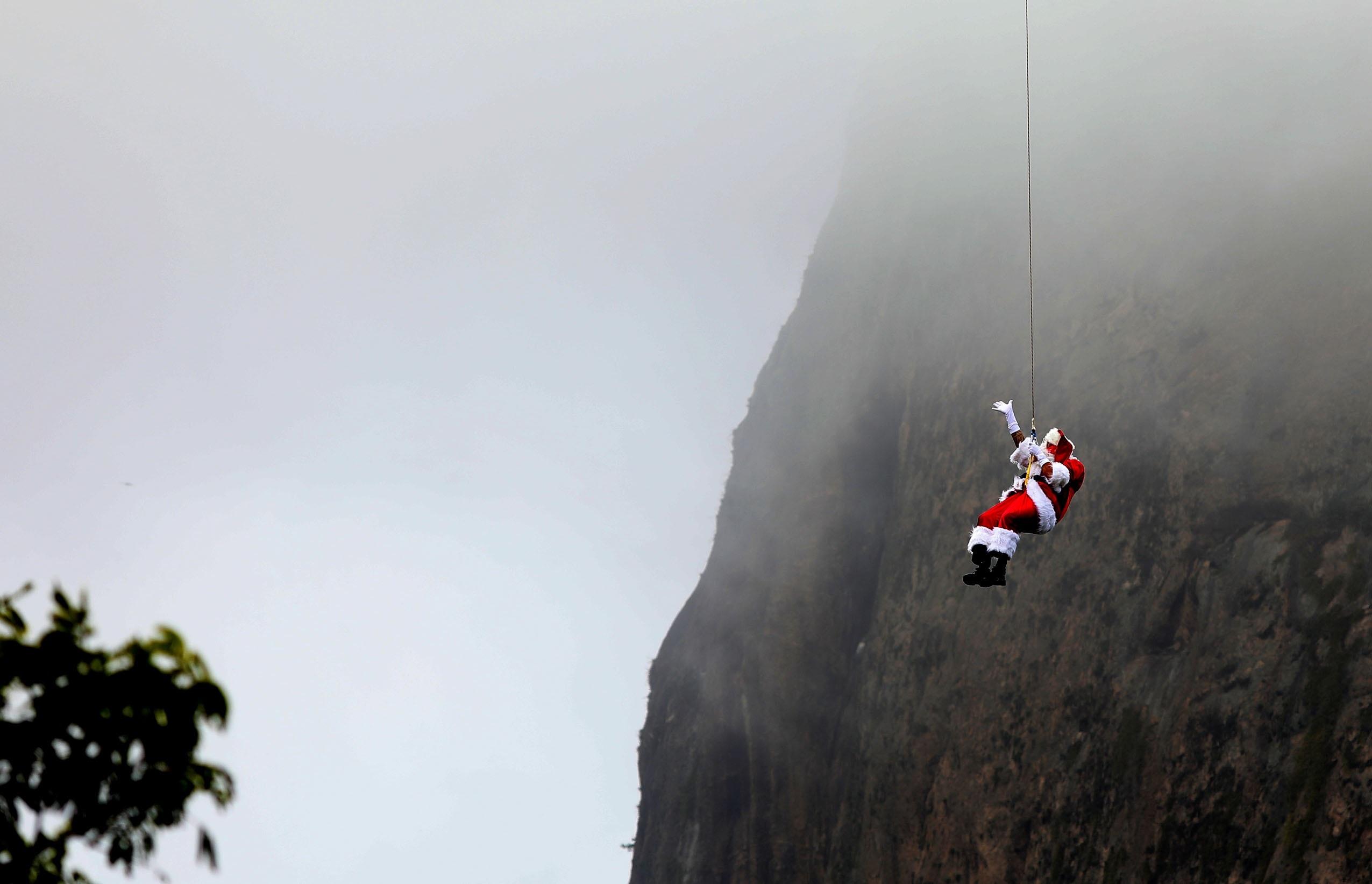 Un hombre vestido de Santa Claus desciende en rápel por el cerro de Pan de Azúcar hoy, en Río de Janeiro, Brasil). EFE/Fabio Motta.