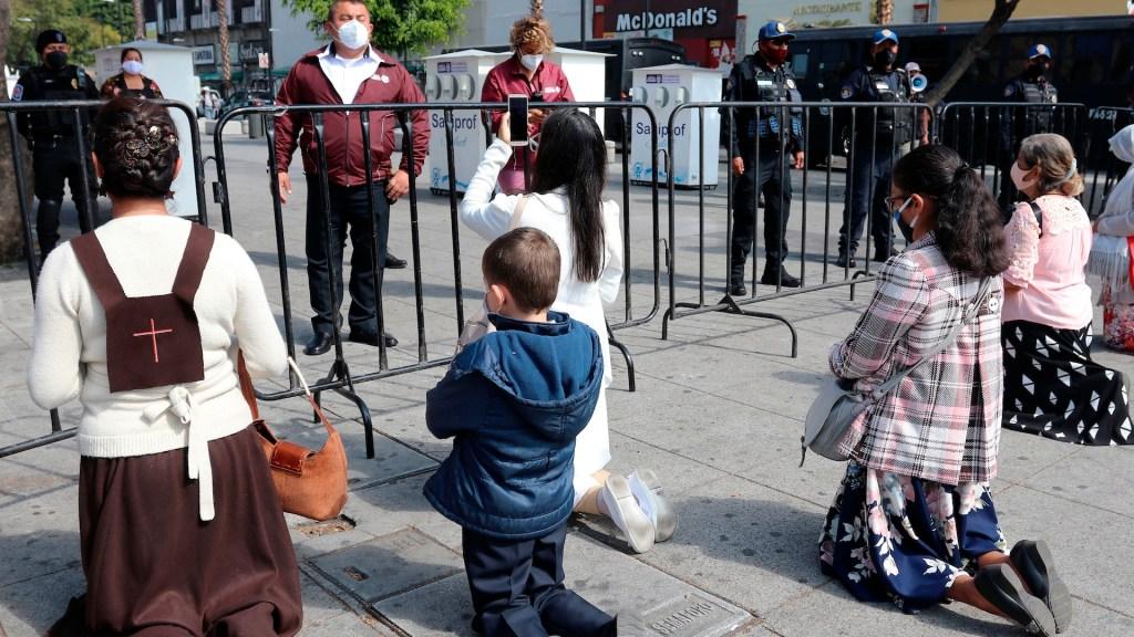 La Virgen de Guadalupe, confinada en su día grande - Personas rezan hoy, afuera de la BasÌlica de Guadalupe de Ciudad de MÈxico (MÈxico). EFE/JosÈ Pazos
