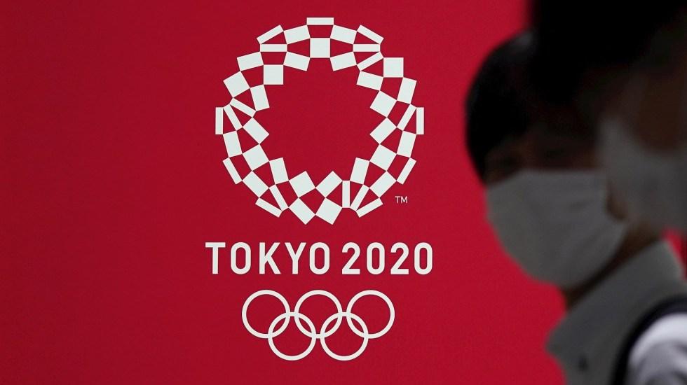 Japón insiste en celebrar Juegos Olímpicos pese a rumores de cancelación - Fotografía de archivo de personas con cubrebocas pasando frente a un cartel con la imagen de los Juegos Olímpicos Tokio 2020 el 15 de julio de 2020 en Tokio, Japón. Foto de EFE/ KIMIMASA MAYAMA.