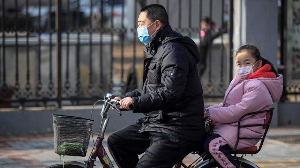 Contagios de COVID-19 continúan en aumento en China tras rebrote en el sur - Padre e hija en bicicleta durante pandemia de COVID-19 en China. Foto de EFE