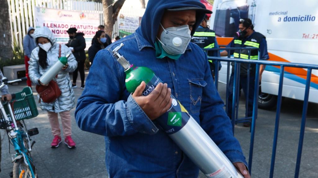 Proponen dar 7 años de cárcel a quien lucre con tanques de oxígeno en CDMX - Personas tras rellenar gratis tanques de oxígeno en Iztapalapa, CDMX. Foto de EFE