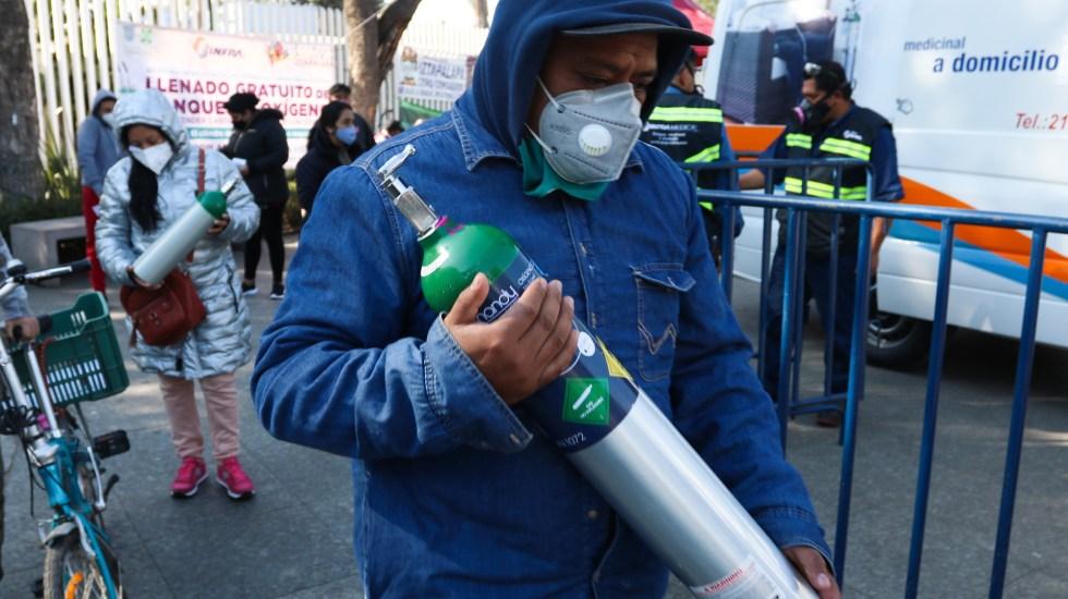 Lanzan campaña para recuperar tanques de oxígeno ante escasez por COVID-19 - Personas tras rellenar gratis tanques de oxígeno en Iztapalapa, CDMX. Foto de EFE