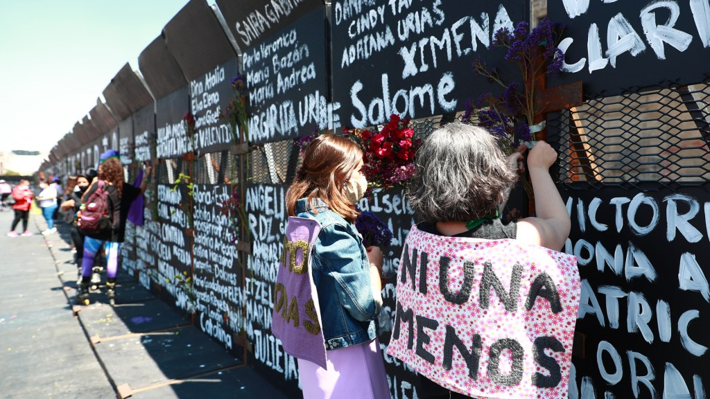 'No soy machista', subraya AMLO; denuncia campaña de desprestigio por vallas de Palacio Nacional - Activistas adornan con flores las vallas que rodean Palacio Nacional y en las que están escritos los nombres de víctimas de feminicidio en México. Foto de EFE