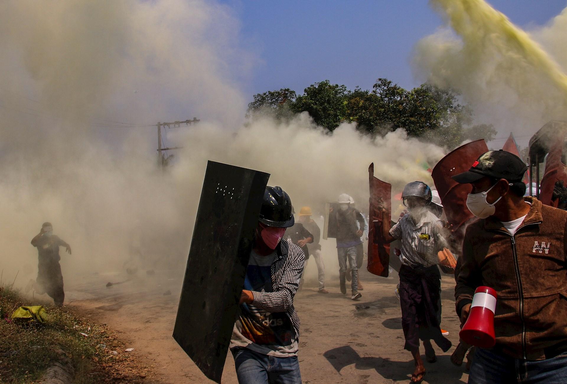 Manifestantes se ponen a salvo del gas lacrimógeno lanzado por la policía durante una nueva jornada de protestas en Naypidó. Dos personas murieron por disparos de la Policía durante una protesta en la ciudad birmana de Myitkyina mientras varias resultaron heridas de gravedad en una nueva jornada de movilizaciones contra la junta militar. Uno de los fallecidos recibió un disparo en la cabeza y el otro en el cuello después de que la Policía cargara contra los manifestantes, informó a Efe un testigo mientras la prensa local habla de más heridos, al menos uno de ellos en estado crítico. Foto de EFE/ Maung Lonlan.