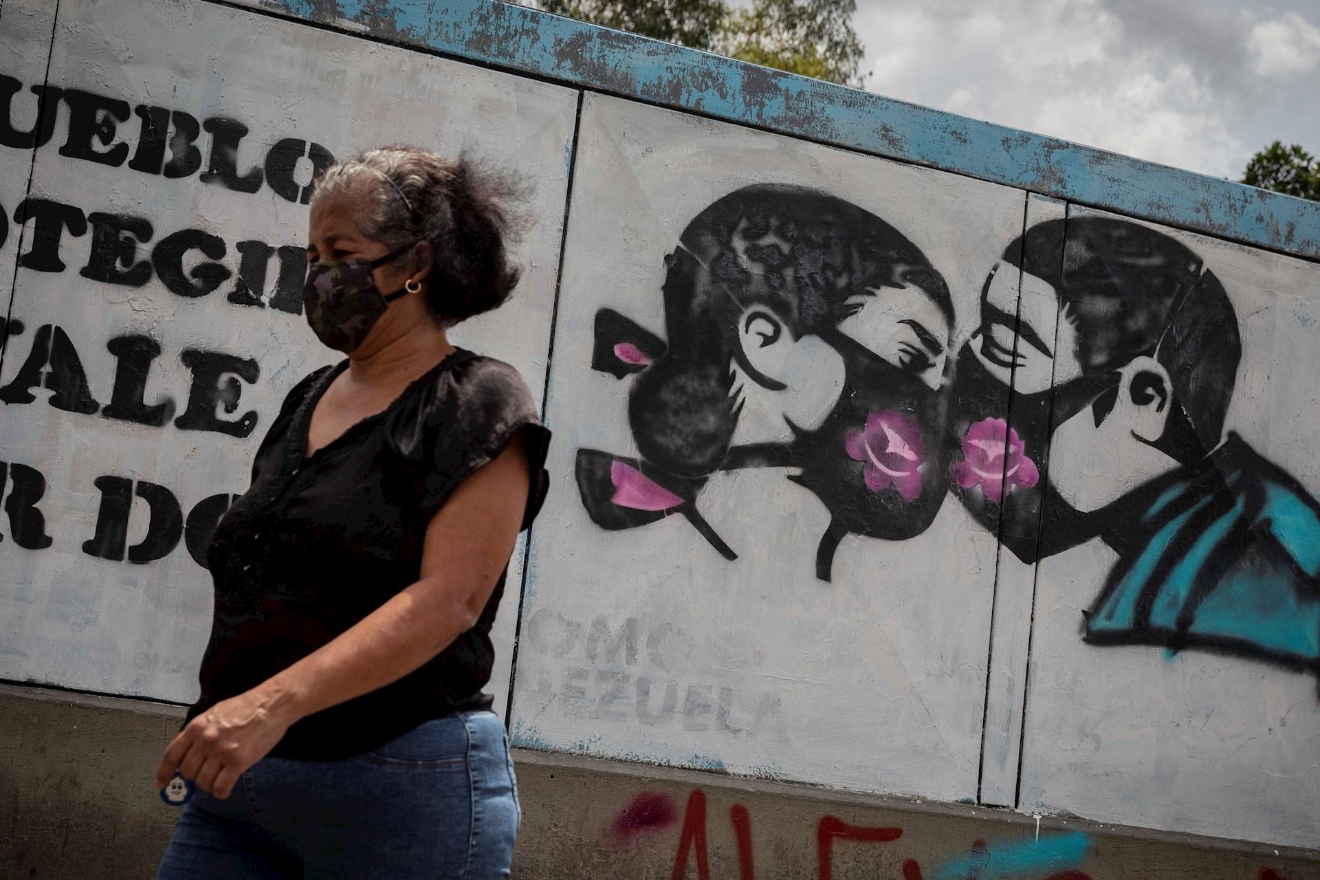 Una mujer camina hoy con tapabocas frente a un grafiti que invita a su correcto uso para evitar la propagación del COVID-19 en Caracas, Venezuela. Foto de EFE/RAYNER PEÑA R.