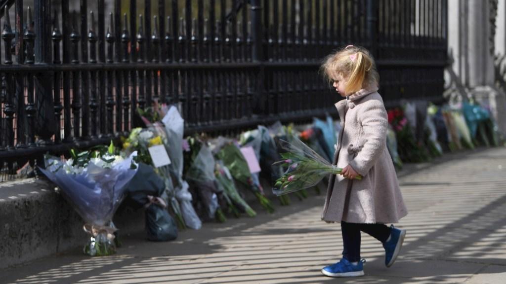 """Los británicos lloran en el Palacio de Buckingham la muerte de su """"abuelo"""", Felipe de Edimburgo - Una niña se dispone a colocar flores a la puertas del Palacio de Buckingham de Londres, en recuerdo del duque Felipe de Edimburgo, fallecido hoy a los 99 años. EFE / EPA / NEIL HALL"""