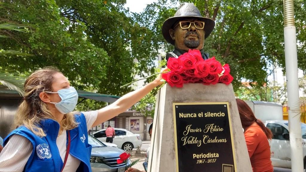 Una mujer coloca un ramo de flores hoy, en el busto del reportero Javier Valdez, en su cuarto aniversario luctuoso, en Culiacán, Sinaloa. Foto de EFE/Juan Carlos Cruz.