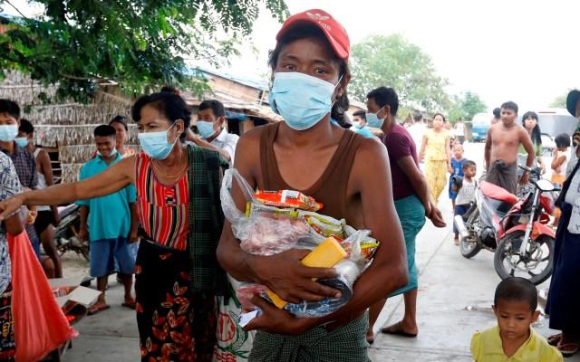 Simpatizantes locales donan comida en Birmania - Un hombre recibe alimentos donados por simpatizantes locales en la zona de tugurios a las afueras de Yangon, Birmania. Según Naciones Unidas, casi 3.5 millones de personas en Birmania pueden tener dificultades para comprar alimentos en los próximos meses en el despertar del golpe militar y la crisis financiera. Foto de EFE