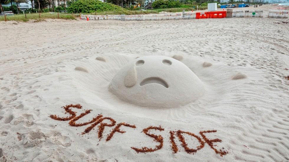 Sube a 94 la cifra de muertos por derrumbe en edificio de Miami-Dade - Una escultura de arena luce una cara triste en el lado este del edificio de condominios Champlain Towers South, parcialmente derrumbado en Surfside, Florida. Hasta el momento se ha confirmado la muerte de 16 personas mientras continúa la búsqueda entre los escombros de personas desaparecidas. Foto de EFE