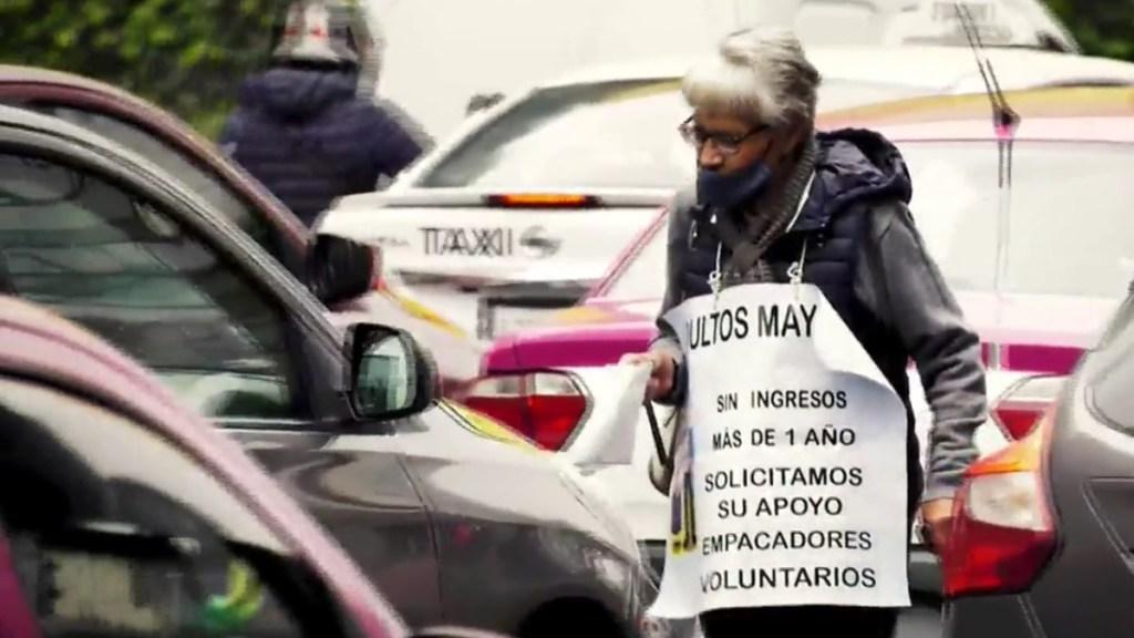 Adultos mayores 'botean' en las calles en espera de volver a supermercados como empacadores - Adulta mayor pide dinero en las calles de la CDMX. Captura de pantalla / Noticieros Televisa