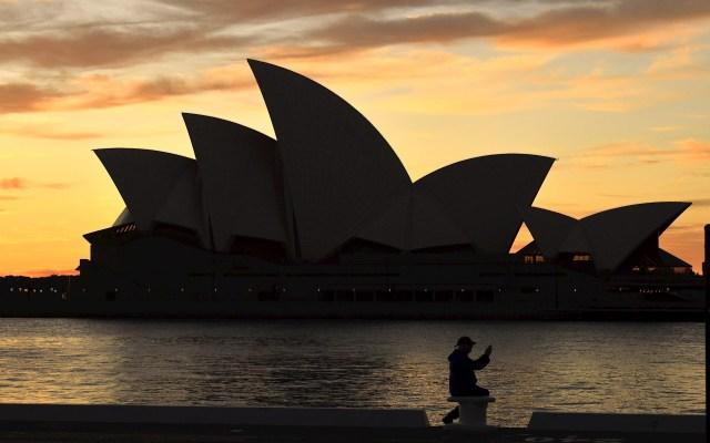 Sídney sale de la cuarentena tras más de cien días de confinamiento - Un ciudadano sentado delante del Teatro de la Ópera de Sídney, Australia, cuando permanece la orden de confinamiento en la capital para evitar la propagación del COVID-19. Foto de EFE/ Mick Tsikas.