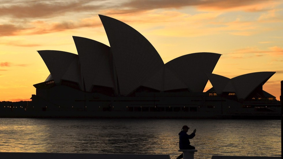 Australia seguirá confinando por la covid aunque vacune a toda su población - Un ciudadano sentado delante del Teatro de la Ópera de Sídney, Australia, cuando permanece la orden de confinamiento en la capital para evitar la propagación del COVID-19. Foto de EFE/ Mick Tsikas.