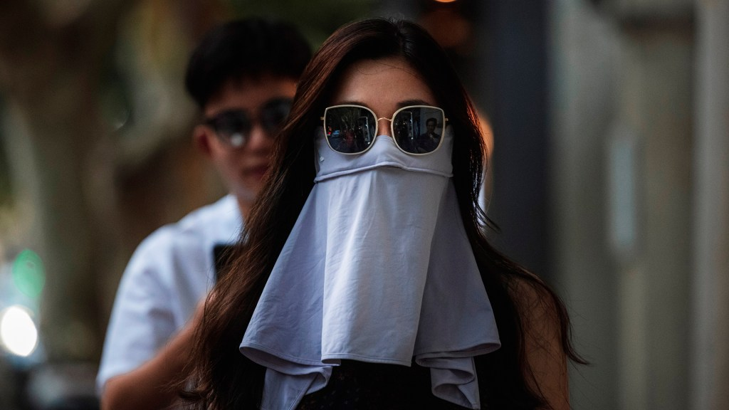 El mundo supera los 200 millones de casos de COVID-19 - Mujer con el rostro parcialmente cubierto con una tela durante la pandemia de COVID-19 en Shanghái