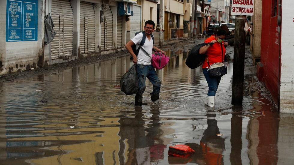 Prevén en Hidalgo aumento de casos de COVID-19 tras inundaciones - Habitantes de Tula caminan entre calles inundadas