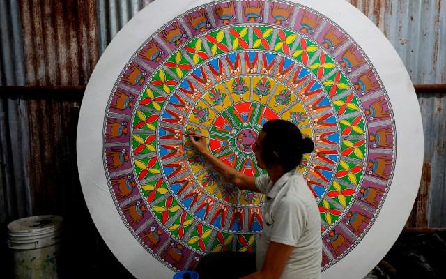 Preparativos del festival Durga Puja en India - El artista indio Sravan Paswan trabaja en una pintura popular de Madhuboni en un pandal hecho con madera, metal y bambú, por los artistas Rupak Basu en Calcuta, India. Bengalíes de todo el mundo celebrarán el festival anual hindú Durga Puja que representa el poder femenino y la victoria del bien sobre el mal. Foto de EFE/ EPA/ PIYAL ADHIKARY.