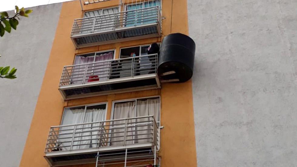 Vecinos de Iztacalco cuelgan tinaco en 5to piso de edificio; PC lo retira - Tinaco en balcón de edificio en Iztacalco. Foto de @IztacalcoAl
