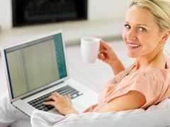 Pretty mature woman having a cup of coffee and using a laptop