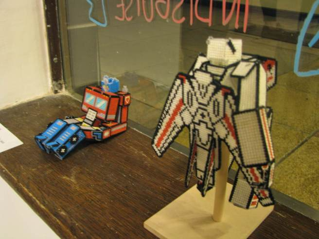 Lord Libidan's Cross Stitch Transformers in window of the Mr X Stitch Exhibition in Bedford (source: mrxstitch.com)
