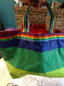 One side of the rainbow striped tote bag made of sail cloth, light green stripe on the bottom with darker green above it and dark blue above it and the a strip of rainbow webbing around the very top