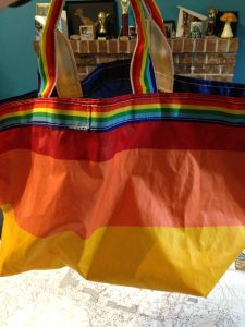 Large tote bag made from rainbow striped sail cloth material, One side of the rainbow striped tote bag made of sail cloth, yellow stripe on the bottom, an orange stripe above it and a red stripe above it. A strip of rainbow webbing around the very top