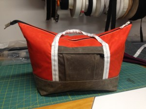 Waxed canvas zip top bag. Orange and brown with white and black notions