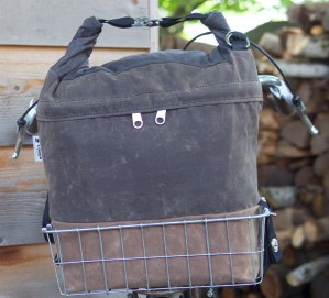Canvas bag with tan bottom brown middle and brown top rolled and connected with 2 metal clips and black strap dangling, in bike basket