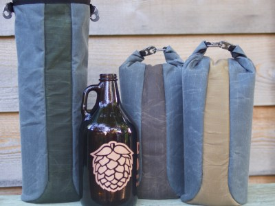 Dark brown beer growler, left bag blue w green strip down center open at top, middle bag blue w brown strip down center and top rolled with 2 metal clips, right bag blue w tan strip and top rolled with 2 metal clips