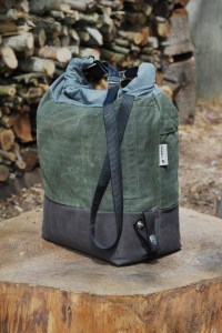 Canvas bag with brown bottom green middle and blue top rolled and connected with 2 metal clips and black strap dangling, on top of tree trunk