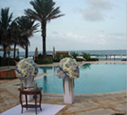 twp blue and white floral arangements on pedestal at poolside, ocean in background
