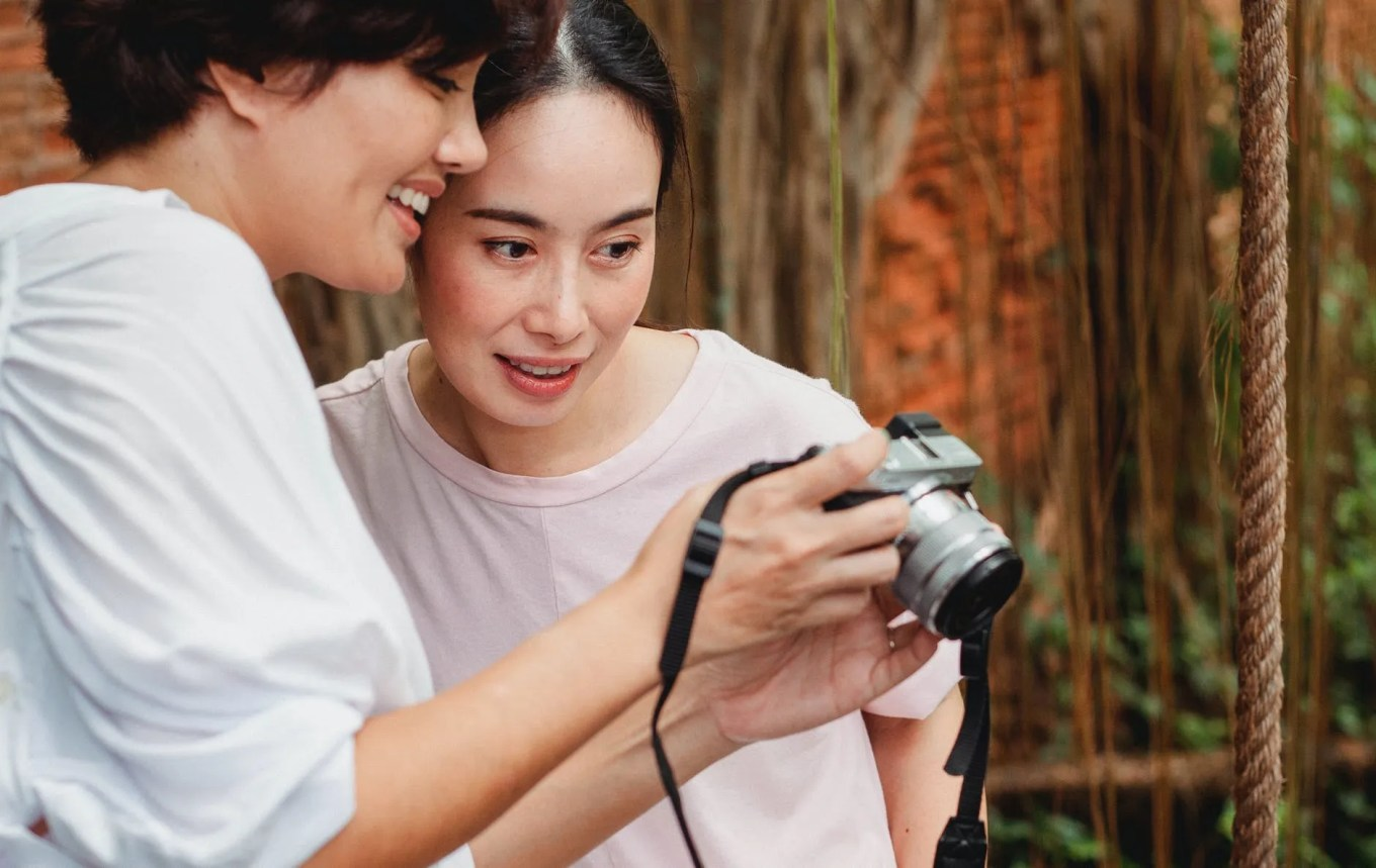 happy asian women looking at screen of photo camera