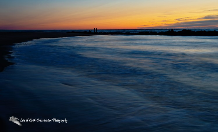 Sunrise over the calm water in front of the jetty at Buckroe Beach in Hampton, Virginia.