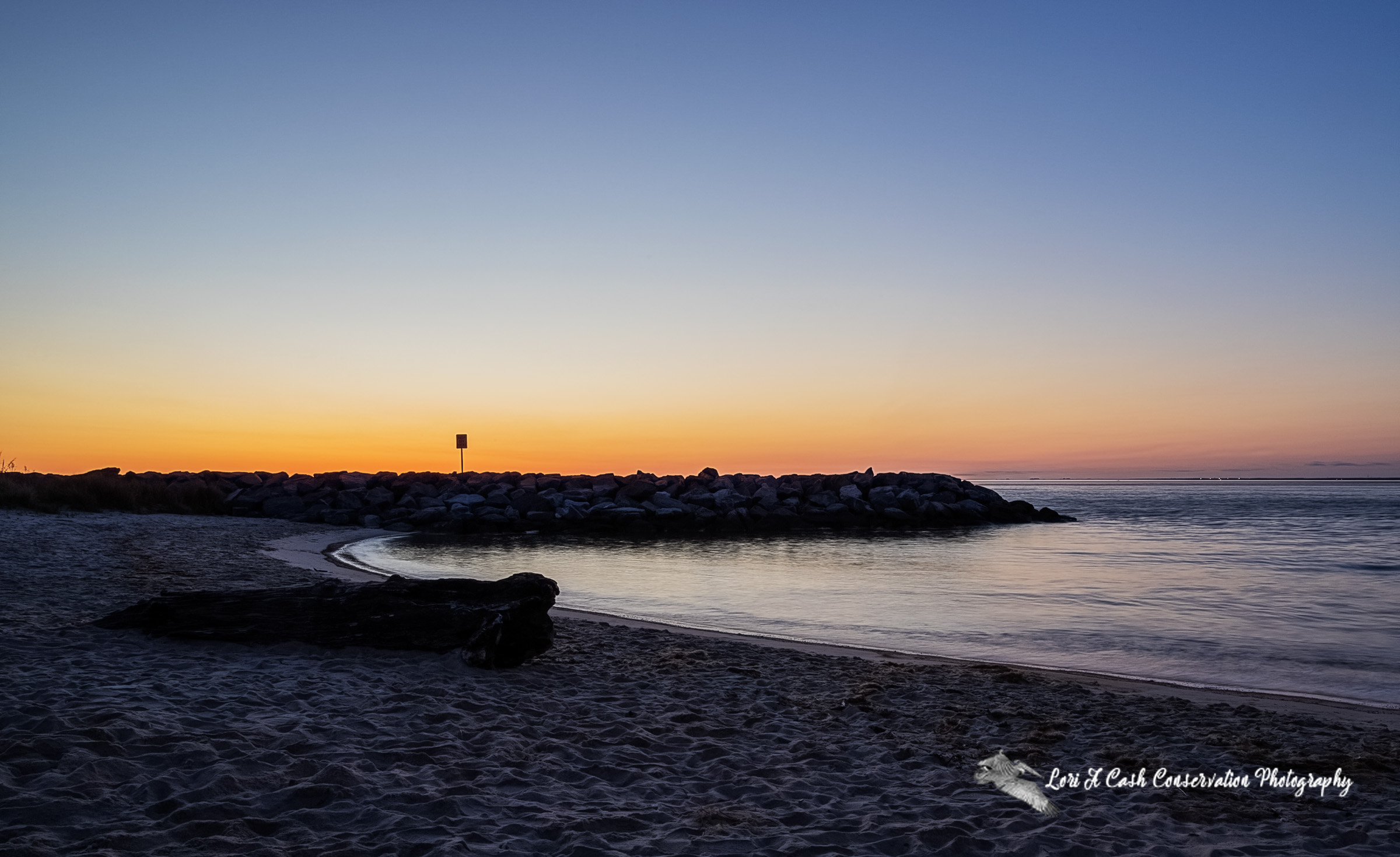 Sunrise in the spring time with orange and blue skies over the rock jetty at Fort Monroe Beach on Fort Monroe National Monument in Hampton, Virginia.