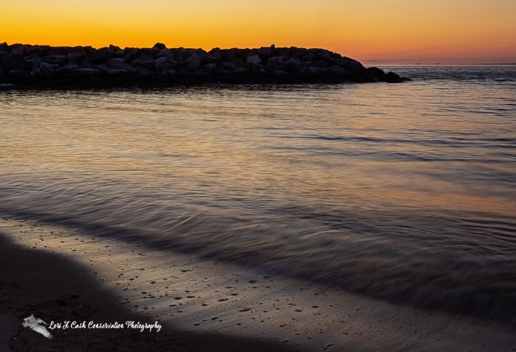 Sunrise over a rock jetty with the calm smooth water in front of it with orange skies on Fort Monroe Beach on Fort Monroe National Monument in Hampton, Virginia.