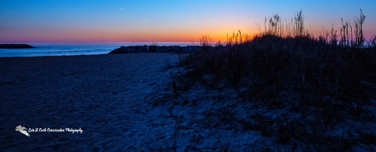 The sunrise along the beach and grasses at the shoreline at Fort Monroe Beach on Fort Monroe in Hampton, Virginia.