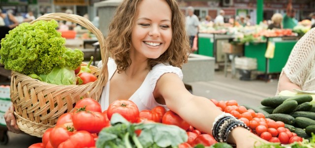 Young woman buying fresh vegetables to support her microbiome and mood