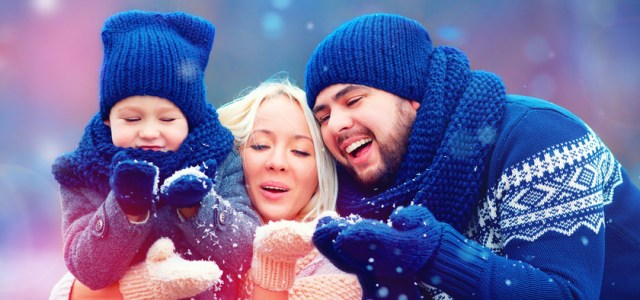 Photo of family catching snowflakes who have found happiness in their relationships illustrates the social principle of the Science of Happiness.