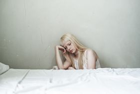 This young woman dozing next to a bed may suffer from insomnia and suicide.