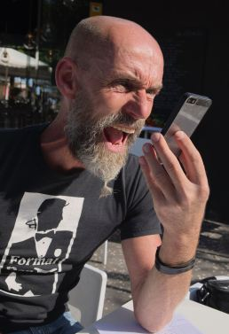 This man shouts into his phone because his amygdala tells him to fight.